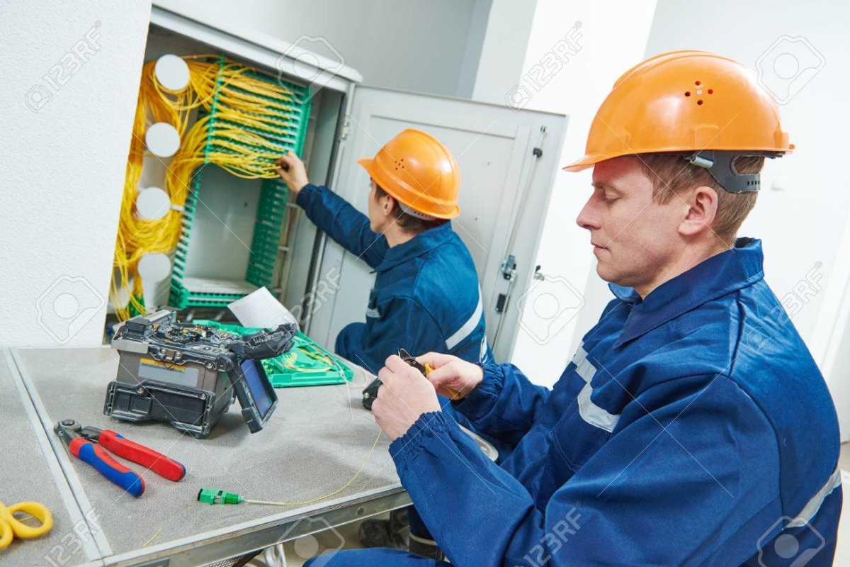 65858334-conexión-a-internet-ingeniero-técnico-que-trabaja-con-la-máquina-de-empalme-de-la-fusión-de-arco-mientras-se-c - Copy.jpg