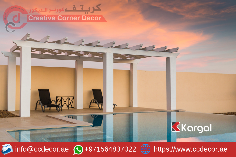 White poolside pergola, gazebo providing shade on a terrace patio area next to an infinity swimming pool at dusk as the sunset turns the sky pink orange.png