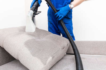 99709086-cleaning-service-man-janitor-in-gloves-and-uniform-vacuum-clean-sofa-with-professional-equipment-.jpg